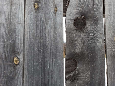 Old wooden fence, gray with age.Darkened boards with round marks from branches.
