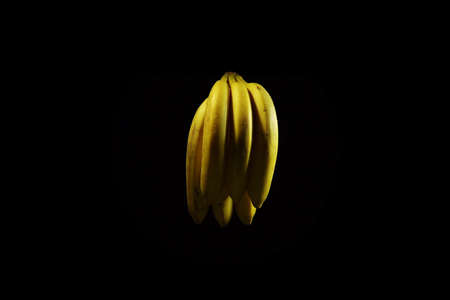 A bunch of ripe yellow bananas with water droplets on a black background.