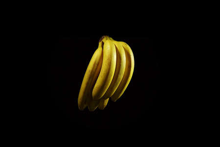 A bunch of six ripe yellow bananas with water droplets isolated on a black background.