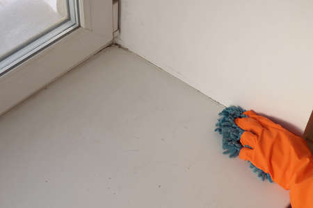 A hand in an orange glove with a blue cloth cleans and disinfects the windowsill from dirt and various infections 写真素材