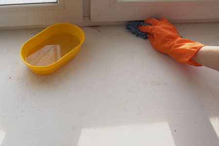 hand in orange glove with blue wet cloth cleans white sill from dust and dirt 写真素材