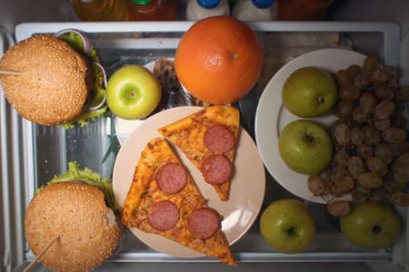 View from above on the shelf of the fridge with fruit burgers and pizza