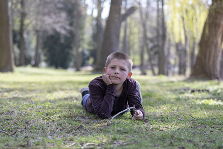 Smiling young boy lying on grass in the park Stock Photo