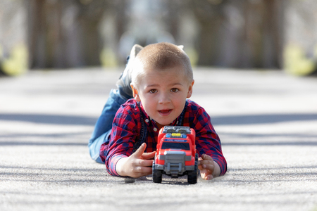 Cute little child, blonde toddler boy playing outdoors lying at street Standard-Bild