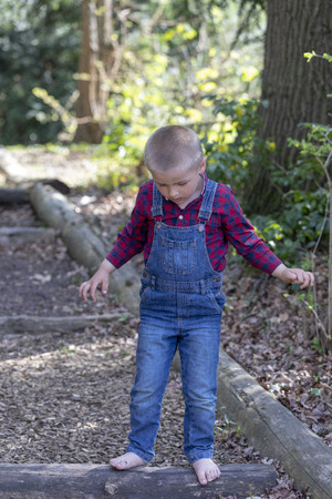A child walks in the park, a denim overall. Evening sunny park. Green grass and trees