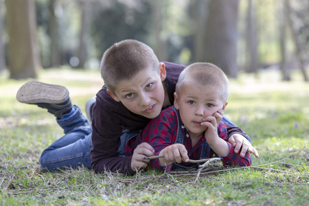 two little blond brothers laying in grass in the spring