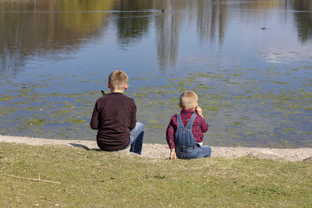 Children sit together at the lake and look out to the water Archivio Fotografico