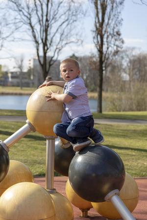 Portrait of a little blond boy on playground.