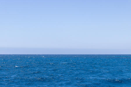 Seascape with sea horizon and almost clear deep blue sky