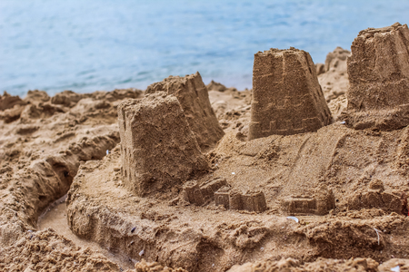 A sandcastle on a sandy beach, set against a bright blue sea water