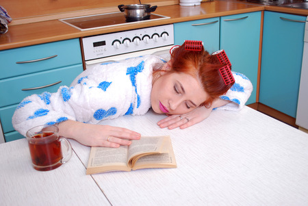 Young attractive housewife was asleep at the kitchen table reading the book