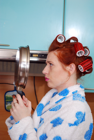 frowned: The young housewife with red hair in kitchen has frowned costs and looks at reflection in a frying pan
