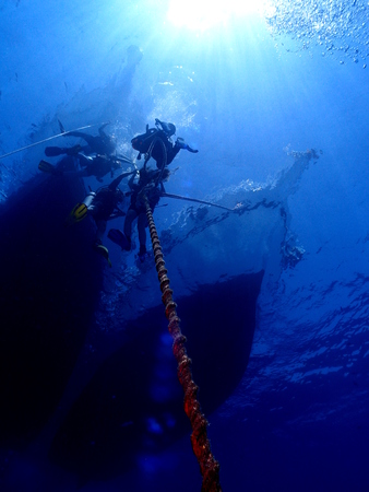 Silhouette of scuba divers and boats Stock Photo