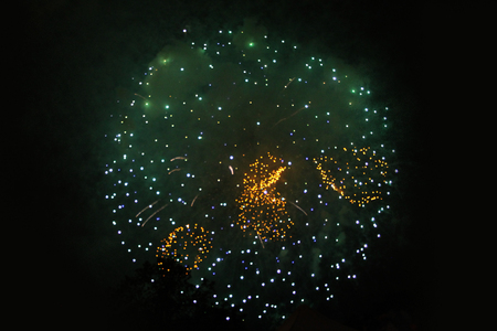 An outbreak of bright green and yellow firework lights. Halloween, Christmas, Independence Day, New Year.
