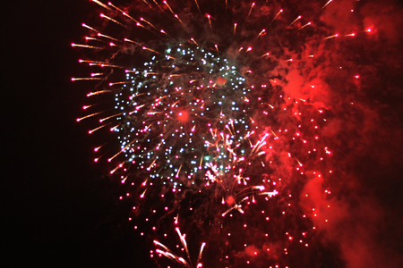 A beautiful explosion of bright red sparkling firework lights during Halloween, Christmas, Independence Day, New Year.