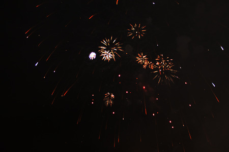 A flash of placers of bright orange sparkling firework sparks during Halloween, Christmas, Independence Day, New Year.