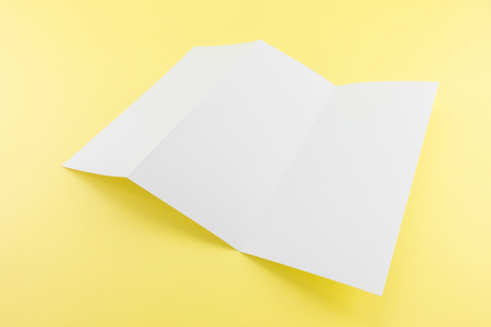 Blank Trifold white template paper on yellow background with soft shadows. Ready for your design. Stock Photo