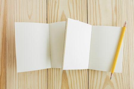 Blank open notebook with lined papers on wood background