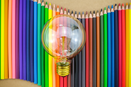 Light bulb on many colorful pencils