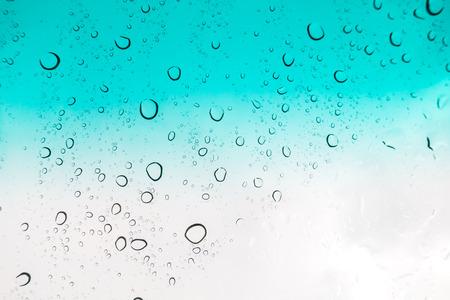 Water drops background. Water drops on glass window over blue sky. Banco de Imagens