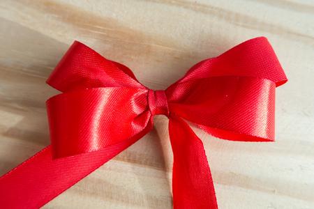 Red ribbon on wood background Banco de Imagens