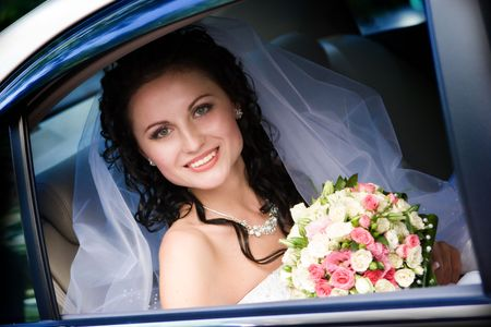 Portrait of the smiling bride sitting in the car