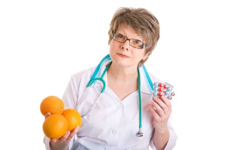stethoskope: smiling doctor with medcines in one hand and oranges in another Stock Photo