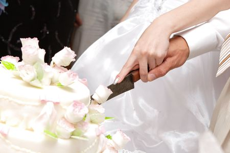 a marriage meeting: hands of bride and groom cut of a slice of a wedding cake Stock Photo