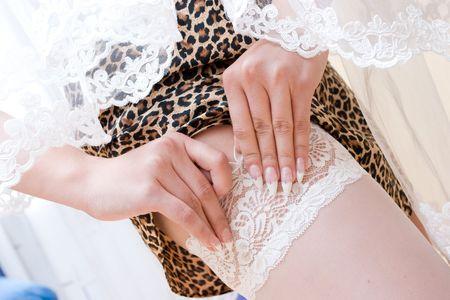 legs around: a bride putting on a stocking Stock Photo