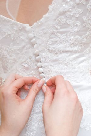 hands of girls help to the bride to button a wedding dress Stock Photo