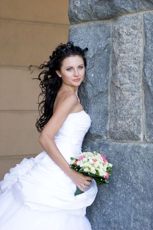a beautiful bride by the stone wall with a bunch of flowers photo