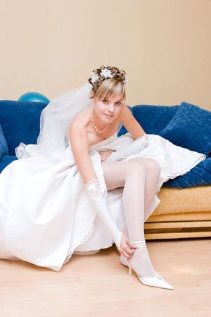 a bride putting on a white shoe