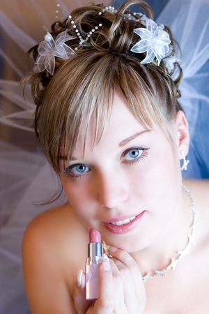 a beautiful bride carefully paints lips with a lipstick