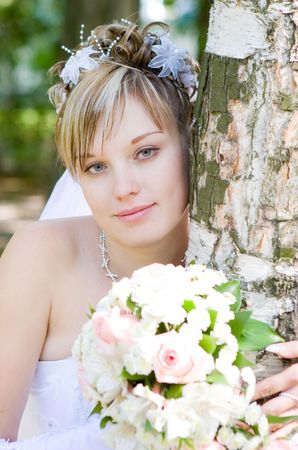 a bride with a flower bouquet embraces a tree photo