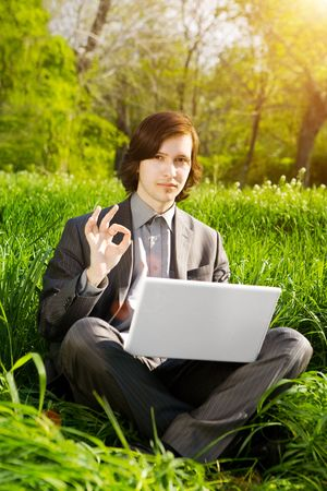a young business man with a laptop on the grass field in sunset photo