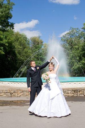 beauty fountain: a bride and a groom danse near the fountain