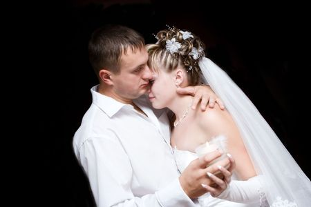 The groom and the bride dance with a burning candle in hands photo