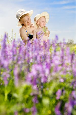 mother and small daughter on the sunny field of wild vetch