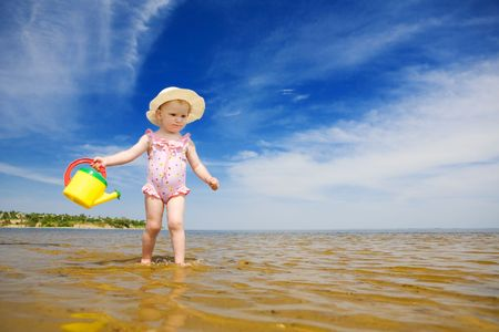 small girl with watering-pot on the seashore photo