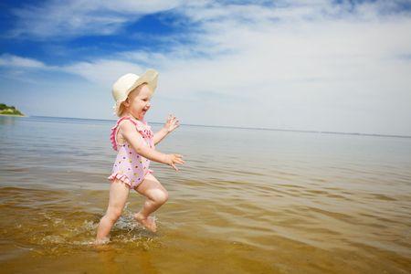 happy girl running in the beach photo