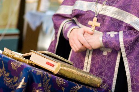 sotana: cruzó las manos del sacerdote orante y un libro abierto
