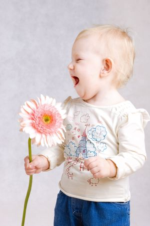 babycare: small girl laughing with flower in hands