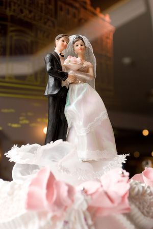 figurines of bride and groom on a wedding cake photo