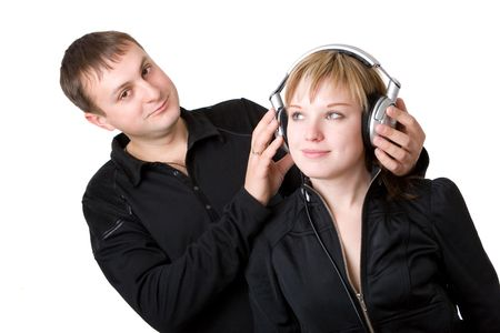Young happy amorous couple with headphones at home photo