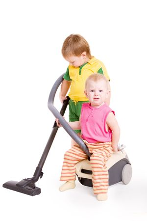 a small girl sitting on Vacuum cleaner and a small boy going in for cleaning photo