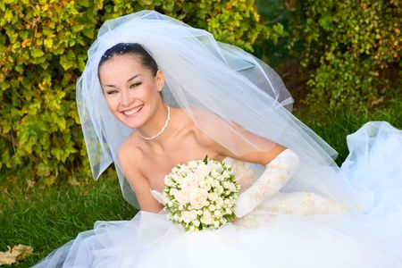 a portrait of the beautiful happy bride under the veil with a flower bouquet in her hands