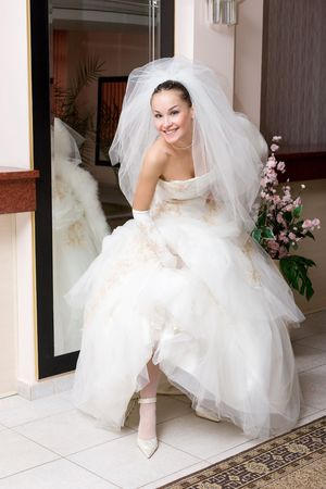 cinderella shoes: happy bride shows a shoe near the big mirror