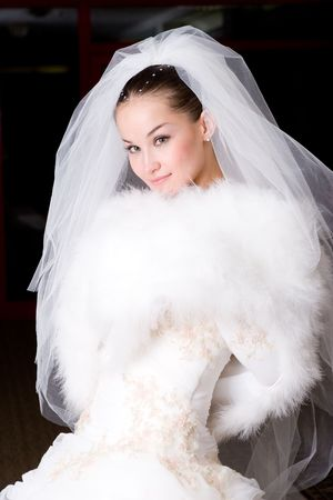 a beautiful bride smiles and covers with a cape Stock Photo