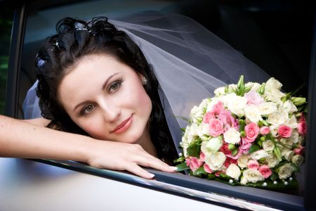 a bride with a bouquet of roses looks out of the car