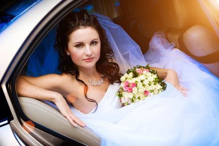 beautiful bride with flowers in the car
